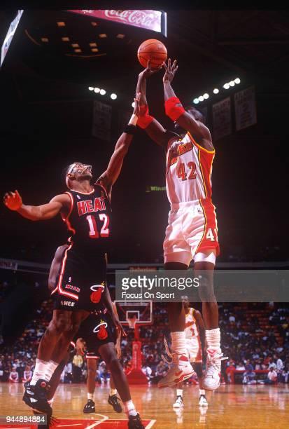 Kevin Willis of the Atlanta Hawks shoots over Bimbo Coles of the Miami Heat during an NBA Basketball game circa 1992 at the Omni Coliseum in Atlanta...