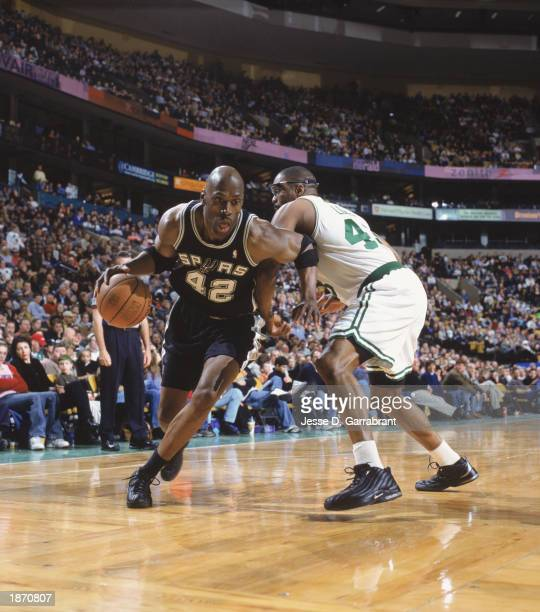 Kevin Willis of the San Antonio Spurs drives past Grant Long of the Boston Celtics during the game at Fleet Center on March 9 2003 in Boston...