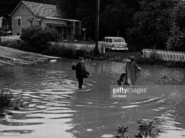 JUL 25 1965 JUL 26 1965 Kevin Yarrow left and brother Greg both of 3130 W Ada Place slosh through muddy waters caused by the cloudburst late Sunday...