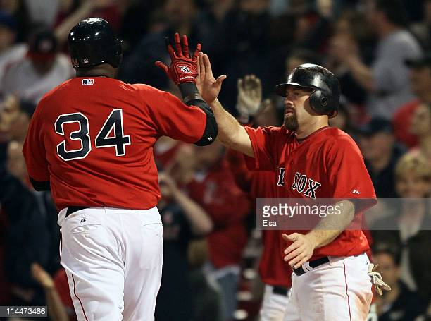 Kevin Youkilis and David Ortiz of the Boston Red Sox celebrate after they scored against the Chicago Cubs on May 20 2011 at Fenway Park in Boston...
