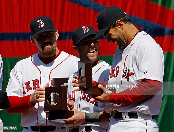 Kevin Youkilis Dustin Pedroia and Mike Lowell of the Boston Red Sox look at their 2007 World Series rings during pregame ceremonies before the Red...