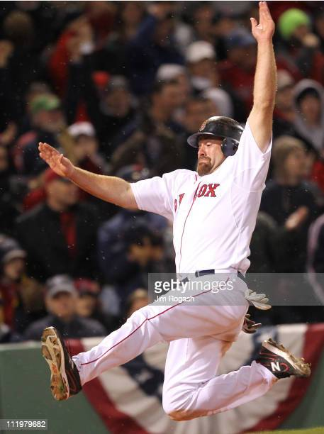 Kevin Youkilis of the Boston Red Sox scores a run on a double hit by David Ortiz against the New York Yankees in the seventh inning at Fenway Park...