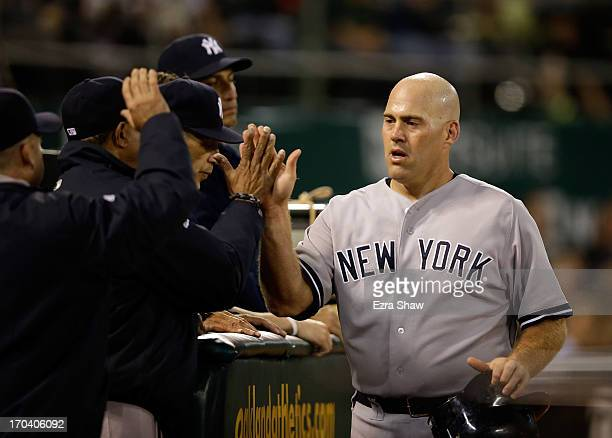 Kevin Youkilis of the New York Yankees is congratulated by teammates after he scored in the seventh inning of their game against the Oakland...