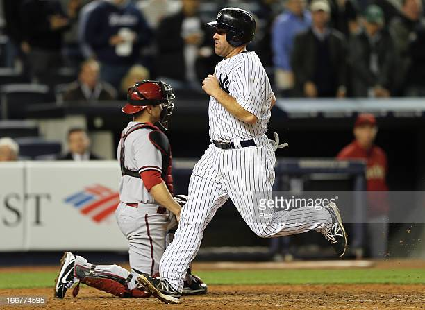 Kevin Youkilis of the New York Yankees scores in the seventh as catcher Miguel Montero of the Arizona Diamondbacks defends on April 16 2013 at Yankee...