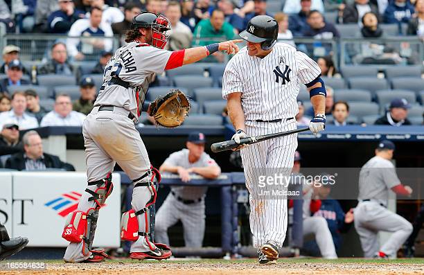 Kevin Youkilis of the New York Yankees strikes out to end the seventh inning as Jarrod Saltalamacchia of the Boston Red Sox points towards his...