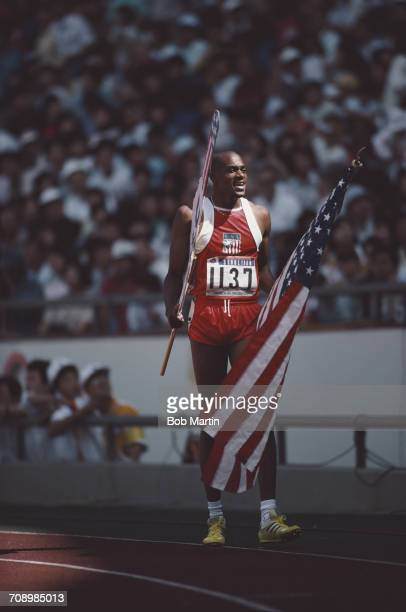 Kevin Young of the United States carries the flag of the United States after finishing in fourth place in the Men's 400 metres Hurdles on 25...
