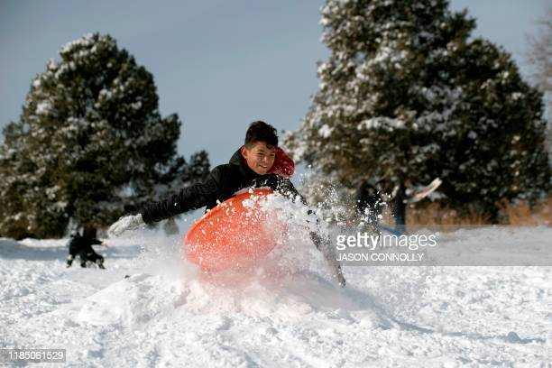 Kevin Zapata catches air while sledding at Ruby Hill Park in Denver Colorado on November 27 2019 A pair of storms packing heavy snow and...