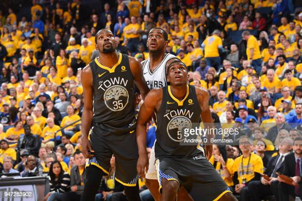 Kevon Looney and Kevin Durant of the Golden State Warriors boxes out against LaMarcus Aldridge of the San Antonio Spurs in Game Two of Round One of...
