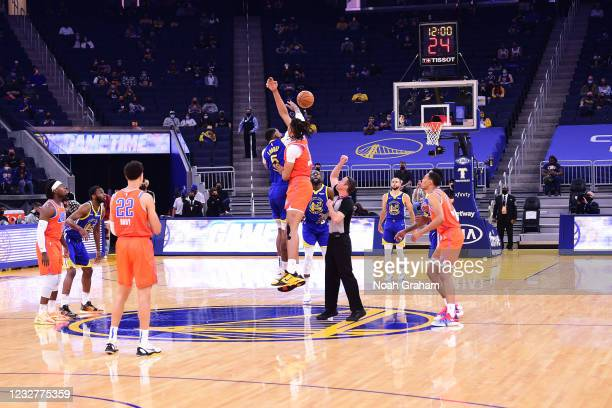 Kevon Looney of the Golden State Warriors and Moses Brown of the Oklahoma City Thunder jump for the tip to start the game on April 8, 2021 at Chase...