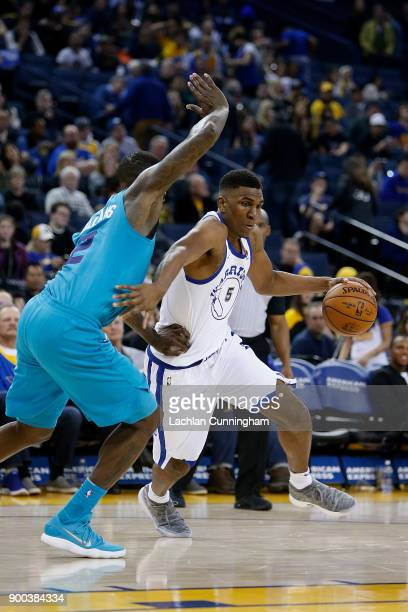 Kevon Looney of the Golden State Warriors drives to the basket against Marvin Williams of the Charlotte Hornets at ORACLE Arena on December 29 2017...