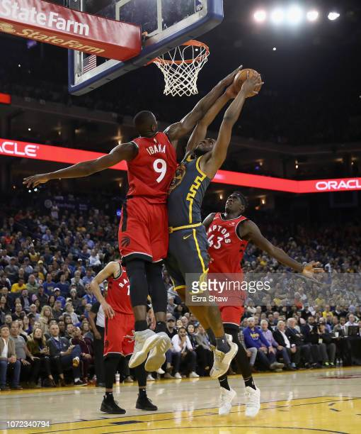 Kevon Looney of the Golden State Warriors goes up for a shot on Serge Ibaka of the Toronto Raptors at ORACLE Arena on December 12 2018 in Oakland...