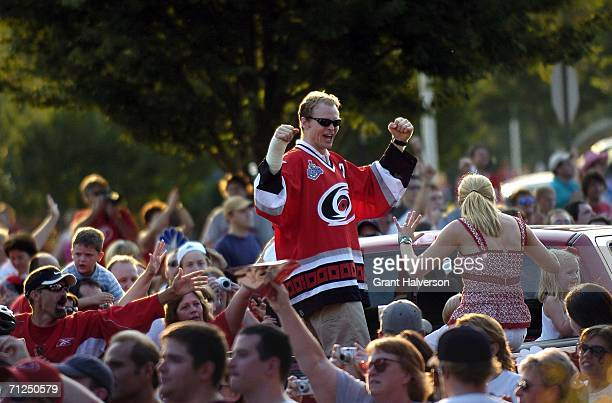 Kevyn Adams of the Carolina Hurricanes celebrates with fans during a parade to celebrate the team's game seven Stanley Cup finals victory over the...
