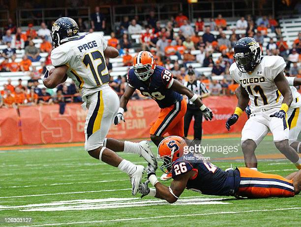 Kevyn Scott of the Syracuse Orange catches the toes of Eric Page of the Toledo Rockets in the game on September 24, 2011 at the Carrier Dome in...
