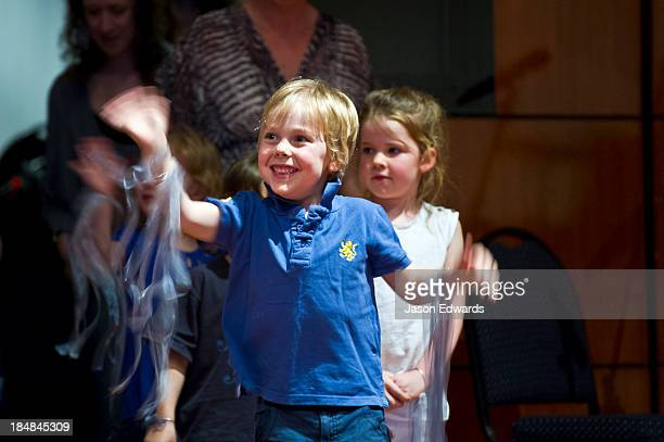 A boy waves to to his parents at a kindergarden school play.