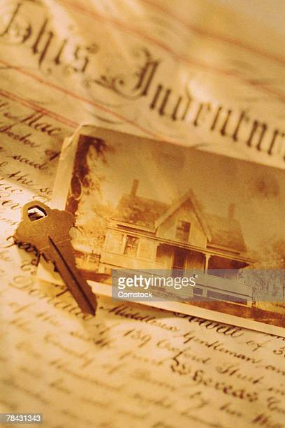 key and photo of house with deed - deed stock photos and pictures