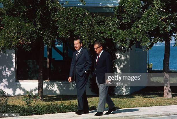 President Richard Nixon and Henry Kissinger stroll around the Florida White House Kissinger met with Nixon before leaving for Vietnam peace talks in...