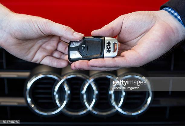 Key handover after a car purchase in a AUDI car dealer in Bonn The photo shows the hands of the seller and of a customer female during the key...