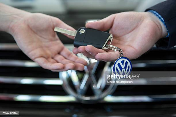 Key handover after a car purchase in a Volkswagen car dealer in Bonn The photo shows the hands of the seller and of a customer female during the key...