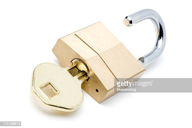 Key inside an open lock on a white background