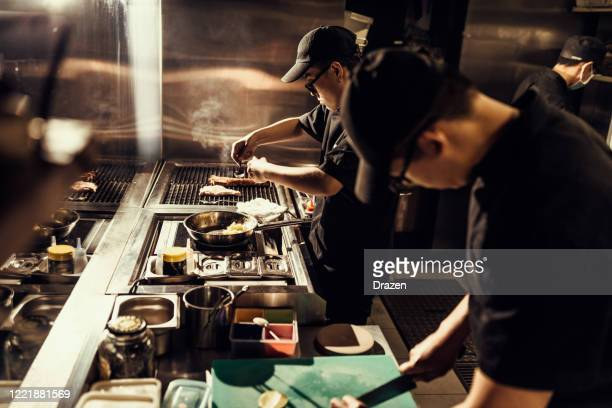 wichtige küchenmitarbeiter bereiten mahlzeiten für die lieferung nach hause vor - gourmet küche stock-fotos und bilder