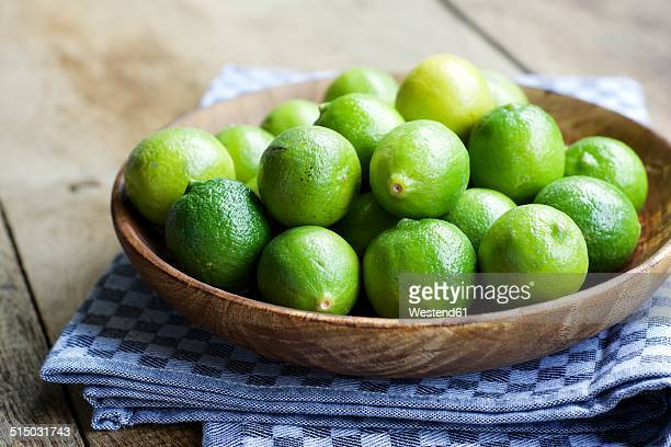 key limes, citrus aurantiifolia, in a wooden bowl - limette stock-fotos und bilder