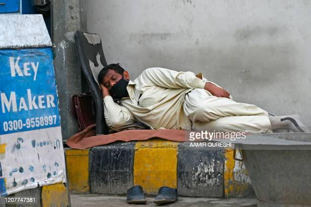 Key maker wearing a facemask amid concerns over the spread of the COVID-19 novel coronavirus, takes a nap alongside a street in Islamabad on March...