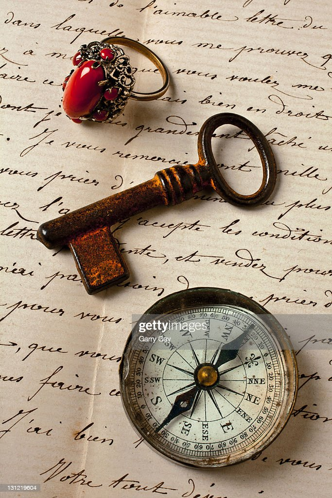Key ring and compass on old letter : Stock Photo