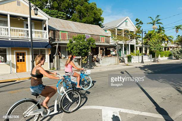key west women bike riders on historic street with architecture - key west stock photos and pictures