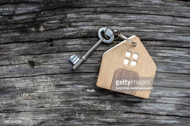 key with shaped house keychain on chain on wood texture background. idea: buying a house, renting, selling real estate. mortgage. - mortgage stock pictures, royalty-free photos & images