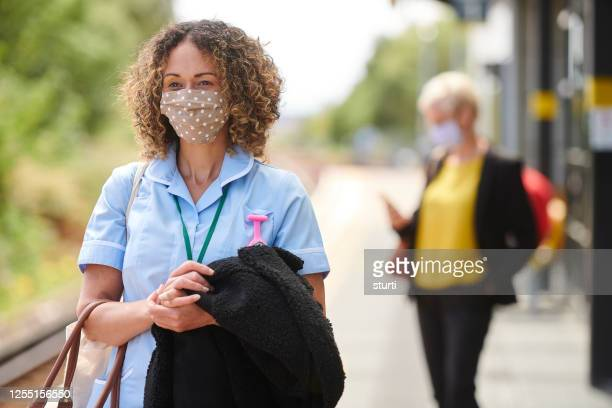 key worker travel with face masks - uk stock pictures, royalty-free photos & images