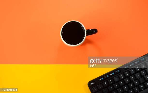 keyboard and coffee - orange background stock pictures, royalty-free photos & images