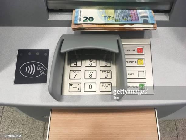 keyboard of an atm with fresh money - geldautomat stock-fotos und bilder