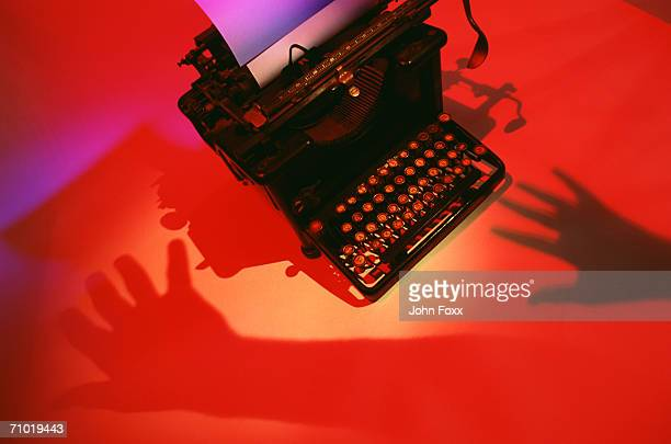 Keyboard of antique typewriter with shadow of hand