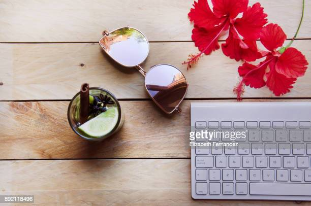 Keyboard, sunglasses, flowers and drink on wooden table