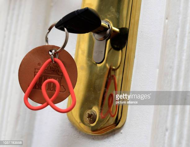 A keychain with the logo of the online platform and community marketplace for private accommodations Airbnb hangs on a key in the door of a vacation...