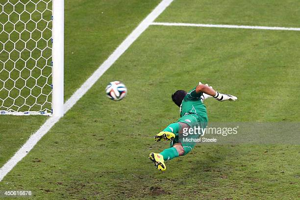 Keylor Navas of Costa Rica dives in vain for a penalty kick goal taken by Edinson Cavani of Uruguay l during the 2014 FIFA World Cup Brazil Group D...