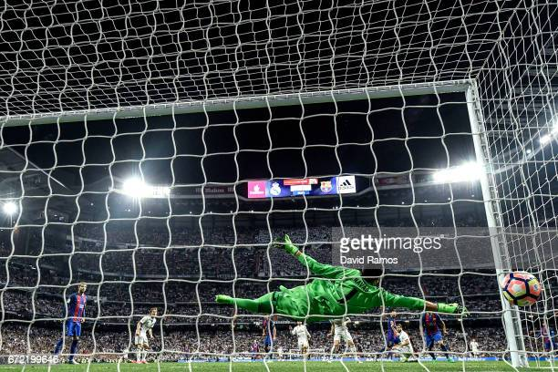 Keylor Navas of Real Madrid CF fails to stop Lionel Messi of FC Barcelona from scoring his team's third goal during the La Liga match between Real...