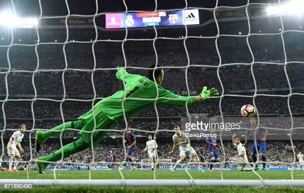 Keylor Navas of Real Madrid fails to stop Lionel Messi of Barcelona from scoring their third goal during the La Liga match between Real Madrid CF and...