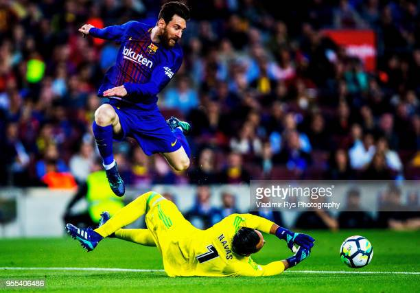 Keylor Navas of Real Madrid makes a save as Lionel Messi of Barcelona jumps over during the La Liga match between FC Barcelona and Real Madrid CF at...