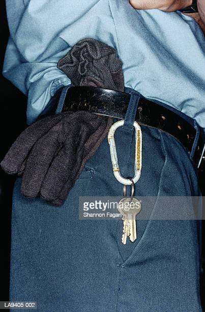 Keys and gloves attached to man's trousers, close-up