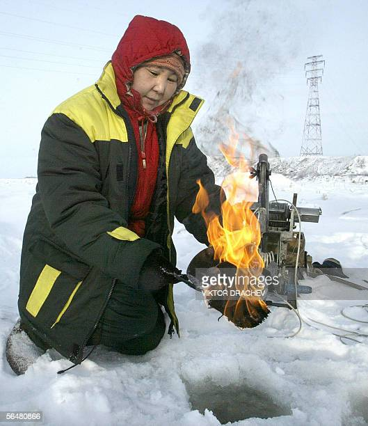 A hydrologist heats up a water analyzer device on the Amur river in Khabarovsk 22 December 2005 Toxic chemicals that contaminated a river after a...