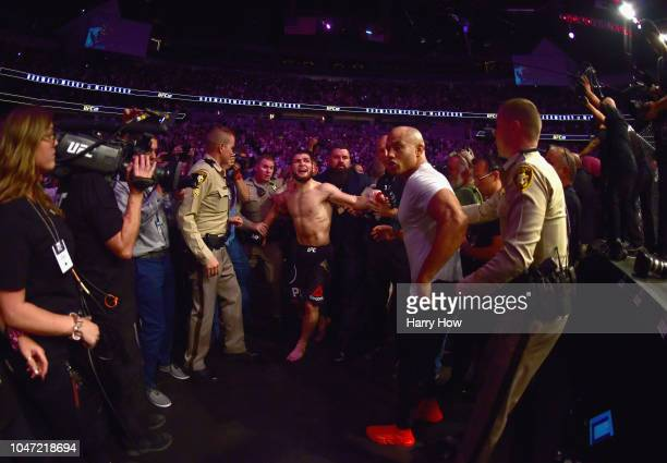 Khabib Nurmagomedov of Russia is escorted out of the arena after defeating Conor McGregor of Ireland in their UFC lightweight championship bout by...