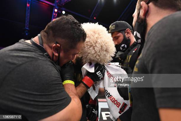 Khabib Nurmagomedov of Russia is surrounded by his team after his victory over Justin Gaethje in their lightweight title bout during the UFC 254...