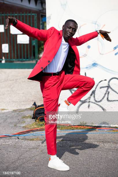 Khaby Lame, wearing red suit, poses ahead of the Boss fashion show during the Milan Fashion Week - Spring / Summer 2022 on September 23, 2021 in...