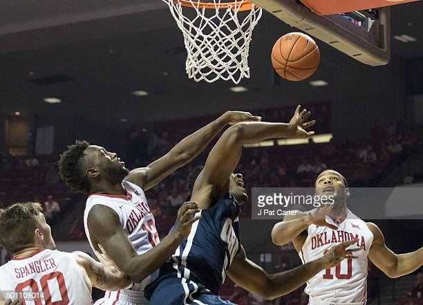 Khadeem Lattin and Jordan Woodard of the Oklahoma Sooners block Brandon Conley of the Oral Roberts Golden Eagles during the first half of NCAA...