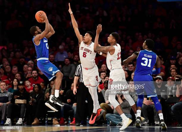 Khadeen Carrington of the Seton Hall Pirates defended by Justin Simon and Tariq Owens of the St. John's Red Storm during the second half an NCAA...