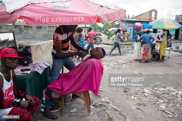 Khaditoza Gola the leader of the Leopard Sapeur group gets a haircut close to his home on February 12 2017 in Kinshasa DRC The word Sapeur comes from...