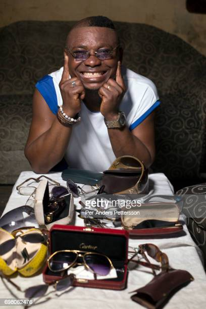 Khaditoza Gola the leader of the Leopard Sapeur shows his big eye glasses collection in his home on February 12 2017 in Kinshasa DRC The word Sapeur...