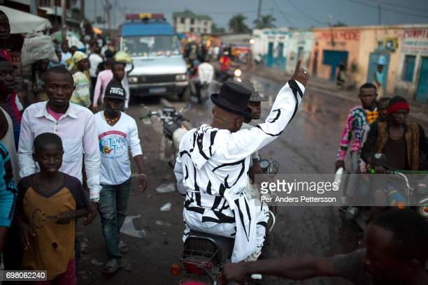 Khaditoza Gola the leader of the Leopard Sapeurs rides on a motorbike close to his home on February 12 2017 in Kinshasa DRC The word Sapeur comes...