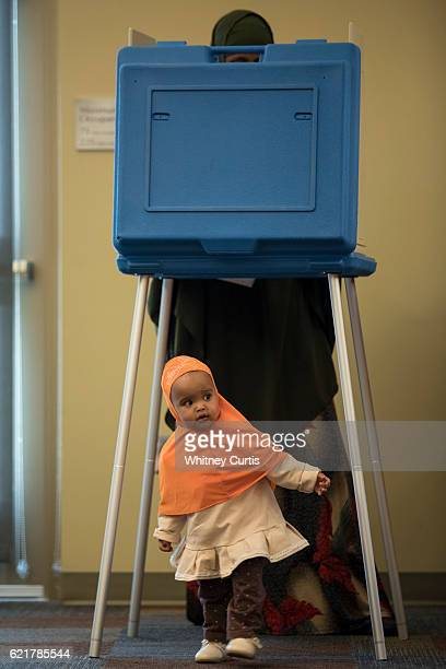 Khadra Guled casts her ballot as Mushtaq her friend's oneyearold daughter plays outside the voting booth on November 8 2016 in Olathe Kansas After a...